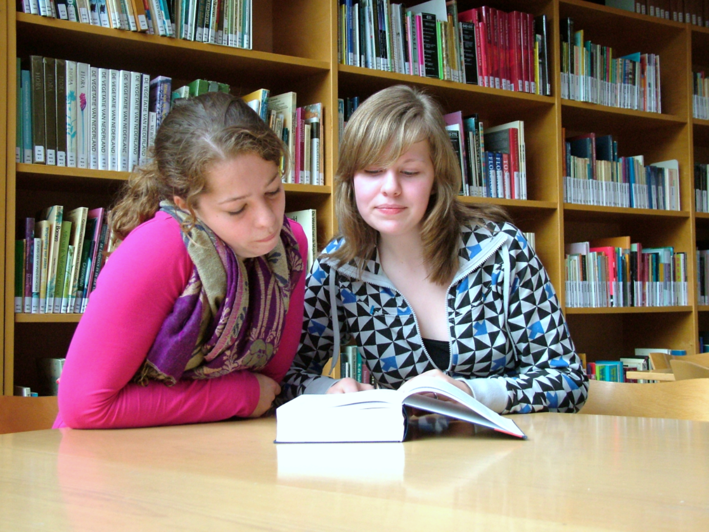 Photograph of a woman tutoring a girl in a library.