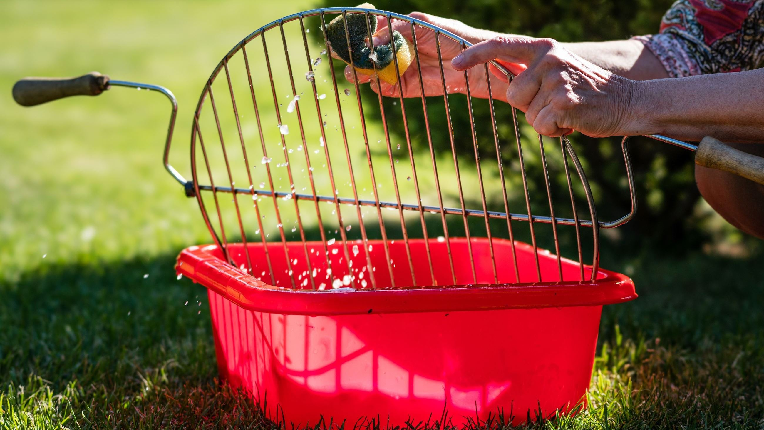 person cleaning a grill grate in a red bucket AdobeStock_204768309