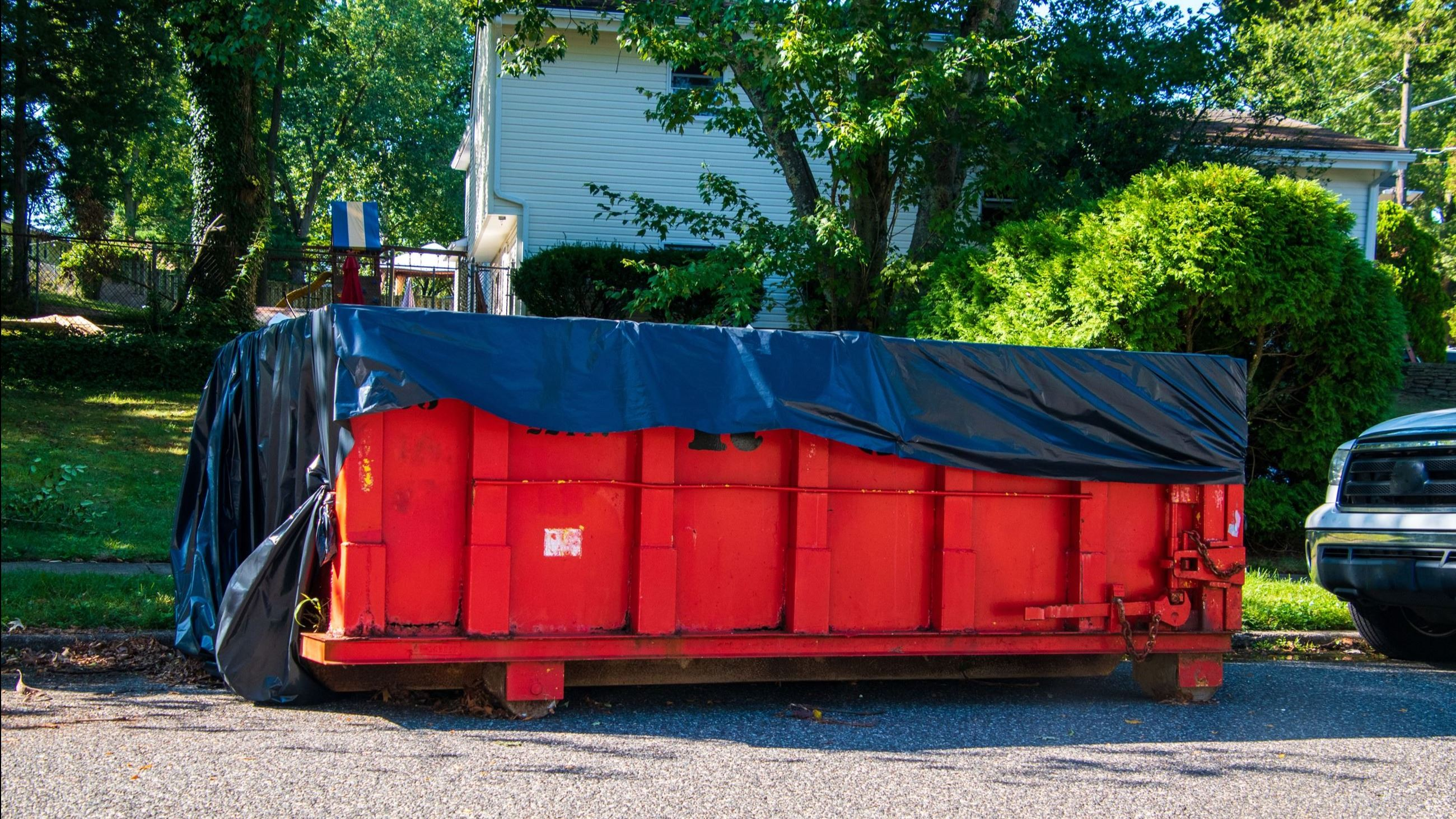 Red dumpster covered with a blue tarp in front of a house AdobeStock_291356110